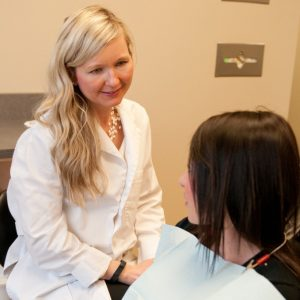 An image of one of Northstar Dental's family dentists, Dr. Kathryn Alderman talking to patient.